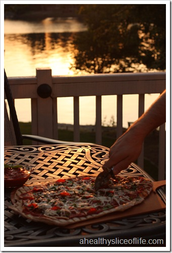 cutting grilled pizza by lake