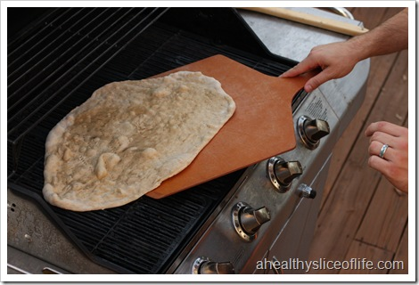 flipping pizza dough on grill