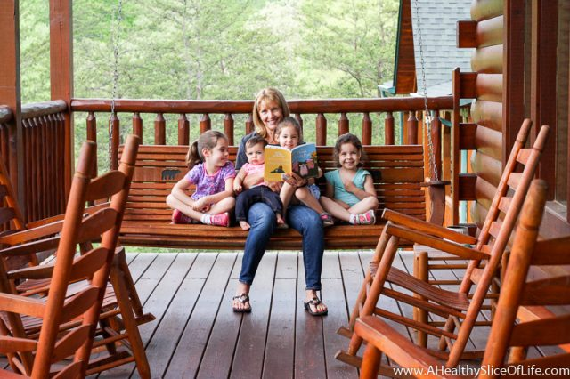 nana reading to girls on porch