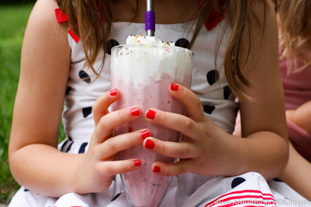 little girl holding milkshake